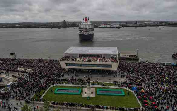 Passengers onboard the Queen Mary 2 wave to the huge crowds gathered along Liverpool's Pier Head to catch a glimpse of Cunard's Three Queens - Queen Mary 2, Queen Elizabeth and Queen Victoria cruise liners - on a historic visit to Liverpool to mark Cunard's 175th anniversary.Photo by James Maloney