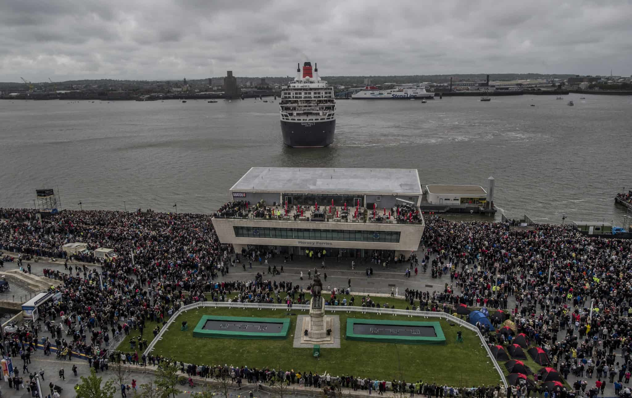 Passengers onboard the Queen Mary 2 wave to the huge crowds gathered along Liverpool's Pier Head to catch a glimpse of Cunard's Three Queens - Queen Mary 2, Queen Elizabeth and Queen Victoria cruise liners - on a historic visit to Liverpool to mark Cunard's 175th anniversary. Photo by James Maloney