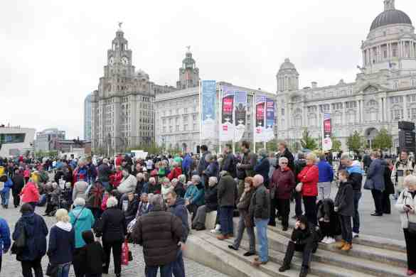 Crowds flock to the waterfront to watch the Queen Mary 2 sail away to meet her two sisters at the mouth of the Mersey before heading back to perform a river dance together during  Cunard's 175 years celebrations.  VT