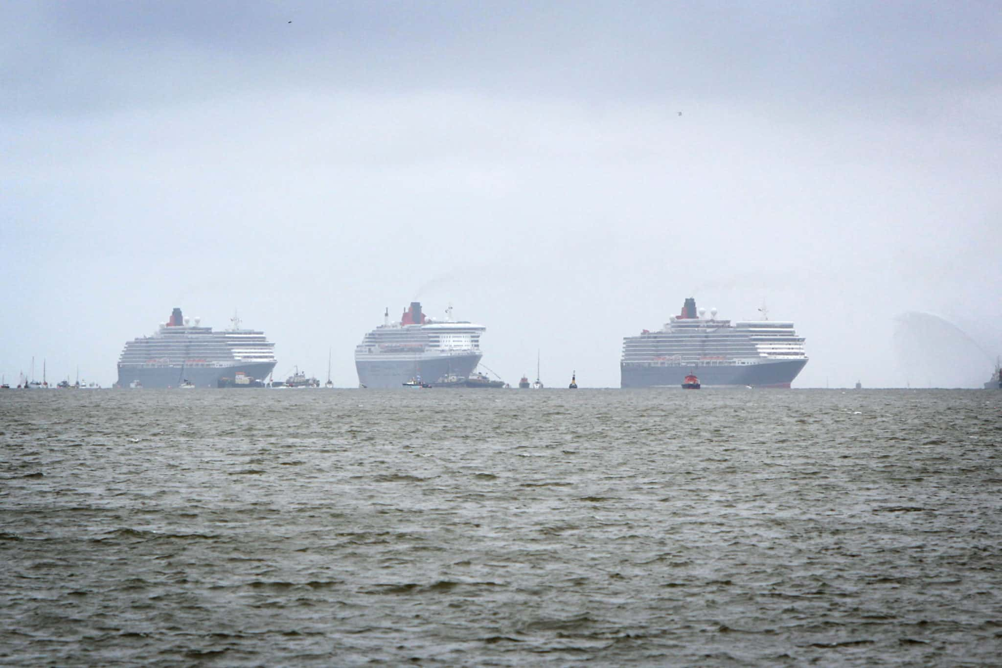 The three queens, Queen Mary 2, Queen Elizabeth and Queen Victoria emerge on the Mersey horizon ready to perform a river dance together during Cunard's 175 years celebrations. VT