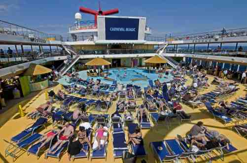Guests aboard the Carnival Magic relax on Lido Deck by the main pool. The area also features Carnival's Seaside Theatre that shows movies and concert videos. Photo by Andy Newman/Carnival Cruise Lines