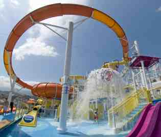 Kids play in Carnival Magic's WaterWorks aqua park and are about to get soaked by water from the Power Drencher, a huge water bucket that periodically dumps 300 gallons of water. The water bucket is part of the a splash zone located within the aqua park that also features a 312-foot-long water slide, the longest in the lineÕs fleet. Photo by Andy Newman/Carnival Cruise Lines