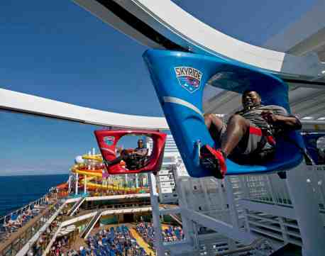 Guests onboard Carnival Vista participate in SkyRide, an opportunity to pedal hanging recumbent-like bikes around an 800-foot-long suspended track some 150 feet above the sea. The largest and most innovative cruise vessel in Carnival Cruise Line's fleet, Carnival Vista measures 133,500 tons, 1,055 feet long and has a guest capacity of almost 4,000 passengers. Photo by Andy Newman/Carnival Cruise Line