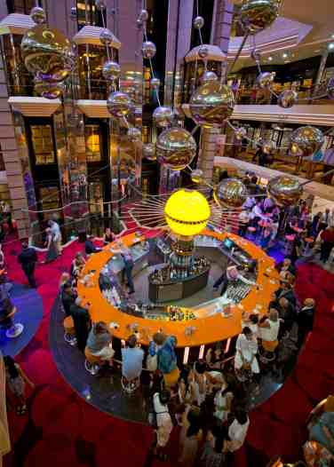 With a backdrop of four glass elevators, guests enjoy cocktails at the Sunshine Bar, located at the first level of the Carnival SunshineÕs towering nine-story atrium. (Andy Newman/Carnival Cruise Lines)