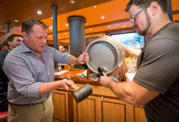 At a Sunday, Jan. 7, 2018, beer-tasting event aboard Carnival Vista at PortMiami, Carnival Cruise Line's Vice President of Beverage Operations Edward Allen (left) and Brewmaster Colin Presby tap the ceremonial keg of a craft beer that will be featured in the Smokehouse Brewhouse restaurant aboard the new Carnival Horizon set to debut this spring.  In addition to craft beers created by Presby, Smokehouse Brewhouse will offer barbecue favorites created by Food Network star and Carnival partner Guy Fieri.Photo by Andy Newman/Carnival Cruise Line
