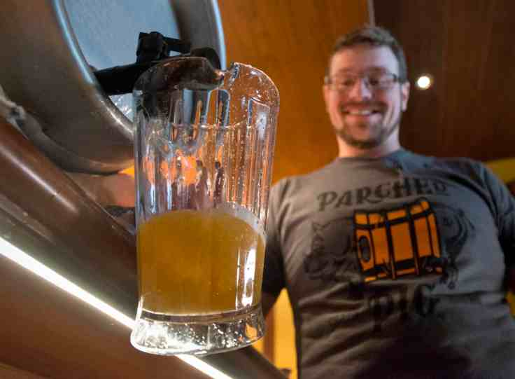 At a Sunday, Jan. 7, 2018, beer-tasting event aboard Carnival Vista at PortMiami, Carnival's Brewmaster Colin Presby pours the first draft of Farmhouse Ale, one of four craft beers that will be featured in the Smokehouse Brewhouse restaurant aboard the new Carnival Horizon set to debut this spring. In addition to craft beers created by Presby, Smokehouse Brewhouse will offer barbecue favorites created by Food Network star and Carnival partner Guy Fieri. Photo by Andy Newman/Carnival Cruise Line