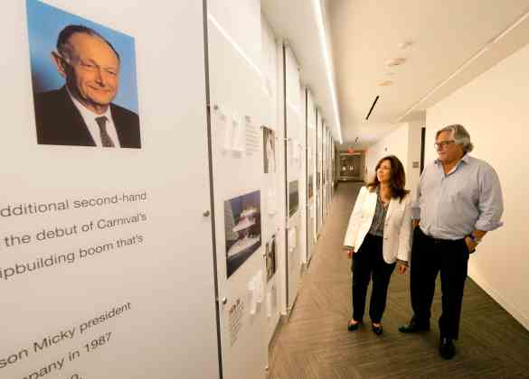 Carnival Cruise Line President Christine Duffy, left, walks with Carnival Corp. Chairman Micky Arison alongside the Timeline Wall outside Carnival Cruise Line's new Fleet Operations Center Thursday, May 10, 2018, at the Miami-based company's headquarters. The photograph, at left, shows the late Ted Arison, Carnival's founder. (Andy Newman/Carnival Cruise Line)
