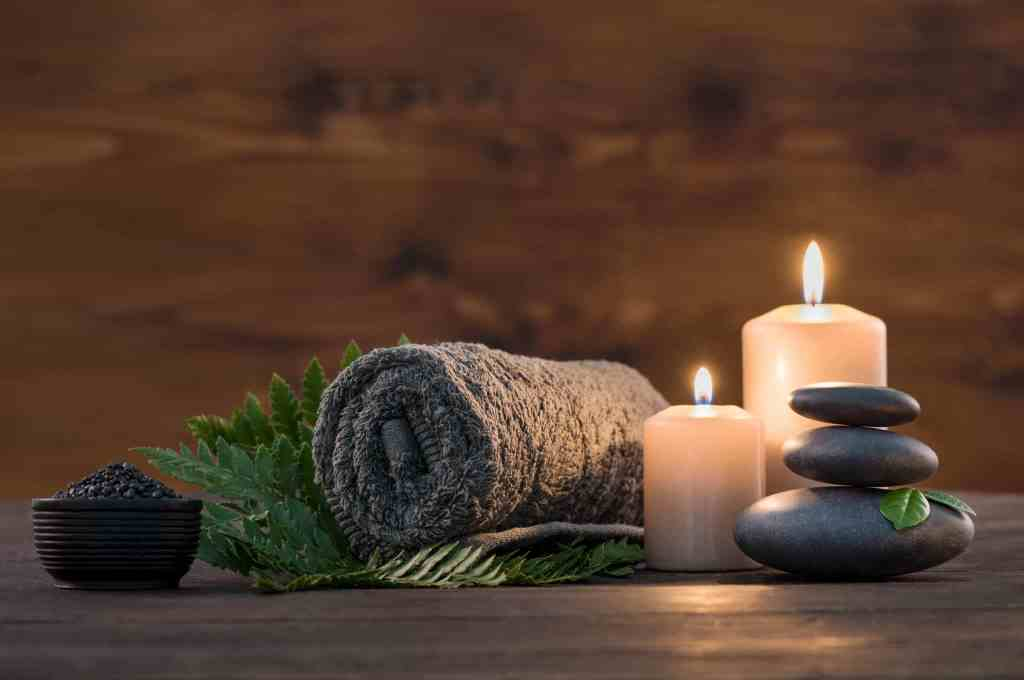 Brown towel on green fern with candles and black hot stone on wooden background.