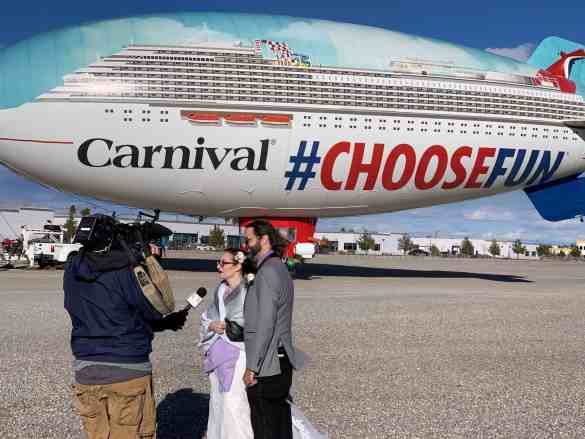 """Love is in the air, indeed! Taking advantage of an """"only in Vegas moment,"""" Carnival Cruise Line's #ChooseFun AirShip hosted its first-ever wedding for Amanda Robertson, 32, and Jason Gerken, 37, from Las Vegas who tied the knot aside the colorful, 128-foot-long blimp."""