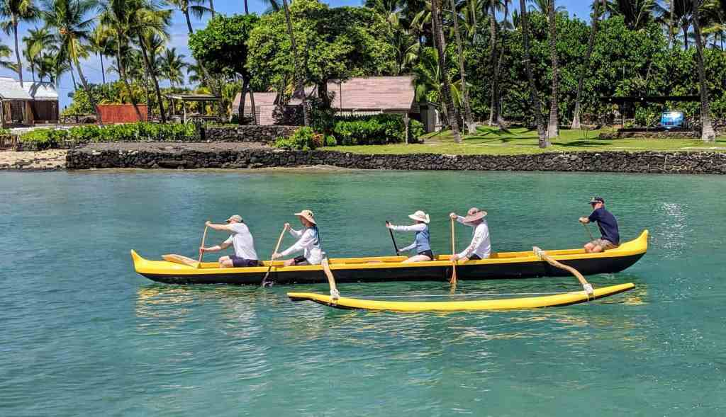 paddling a traditional wooden canoe in Kona