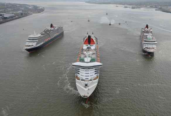 Queen Mary 2, Queen Victoria and Queen Elizabeth meet in the Mersey, Liverpool for a gathering in front of the Three Graces and thousands of people on the riverside.