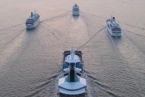 Schiffe der Phoenix-Flotte fahren bei Sonnenuntergang in Formation.