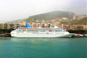 Aus der MAJESTY wird PRINCESS IRIS. Kreuzfahrtschiff THOMSON MAJESTY in Seitenansicht an der Kaimauer von Santa Cruz de Tenerife, dahinter Wohnhäuser und Gebirgslandschaft