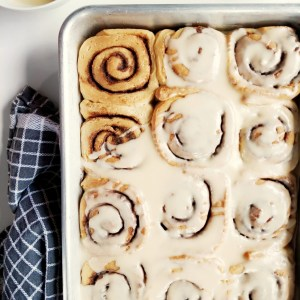 Vegan Brioche Cinnamon Rolls in a baking dish, covered in vanilla glaze