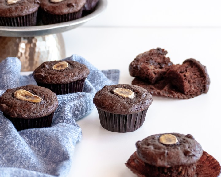 Batch of chocolate banana muffins on table, some on a platter, some with wrappers oof