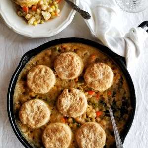 Cast iron skillet filled with chickpea pot pie and flaky biscuits with one serving on a white plate