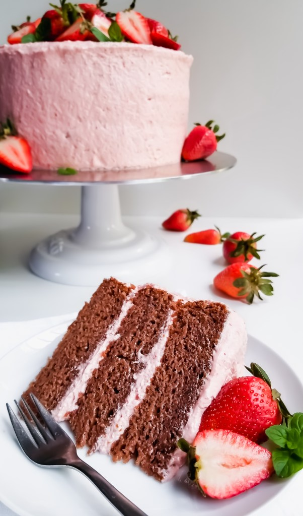 Vegan Strawberry Layer Cake with Strawberry Cream Cheese Frosting sliced and served with fresh strawberries