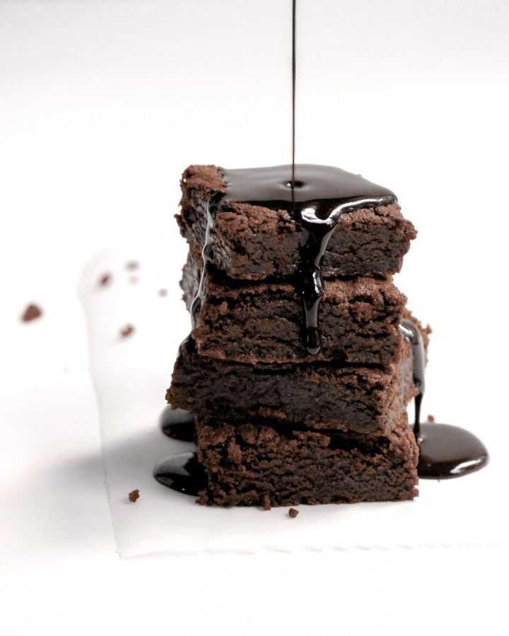 Vegan Brownies in a stack being drizzled with chocolate sauce