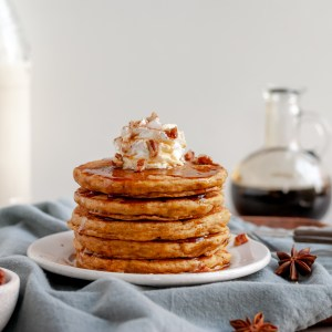 Stack of Spiced Pumpkin and Maple Pancakes topped with coconut whip and maple syrup