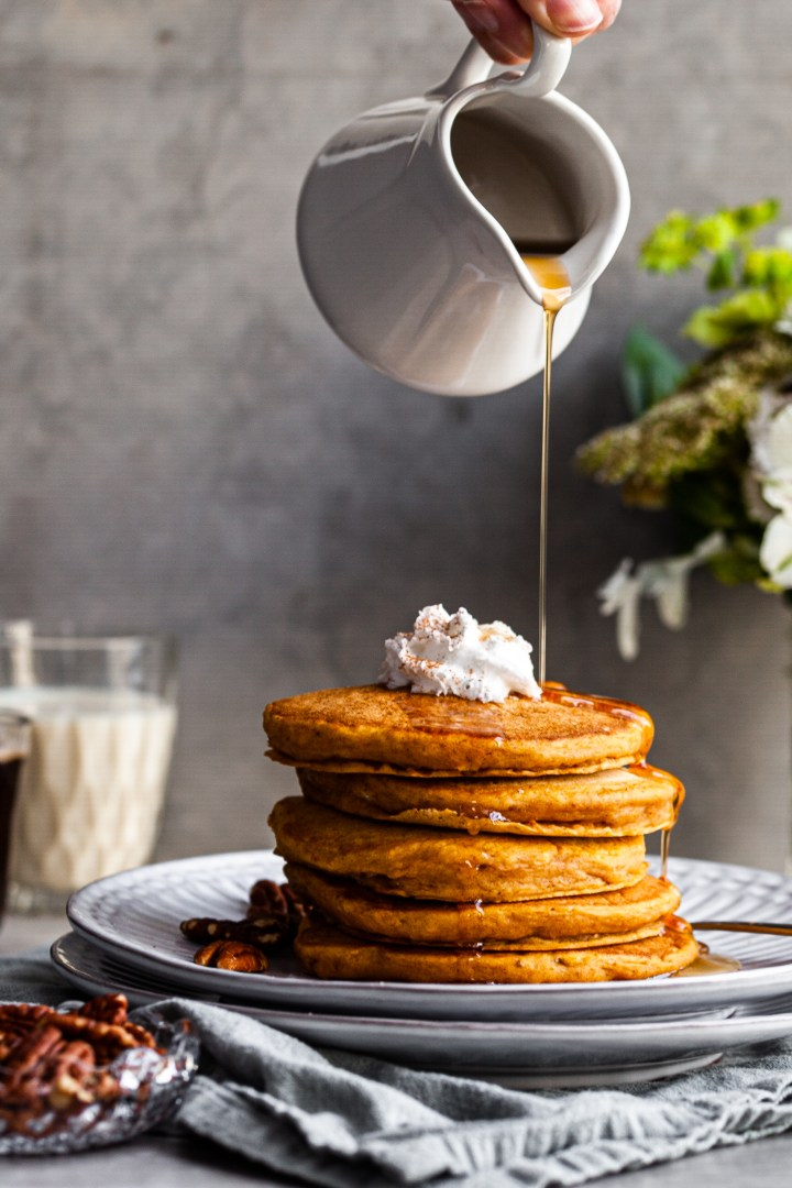 Stack of Pancakes on a plate being drizzled with maple syrup