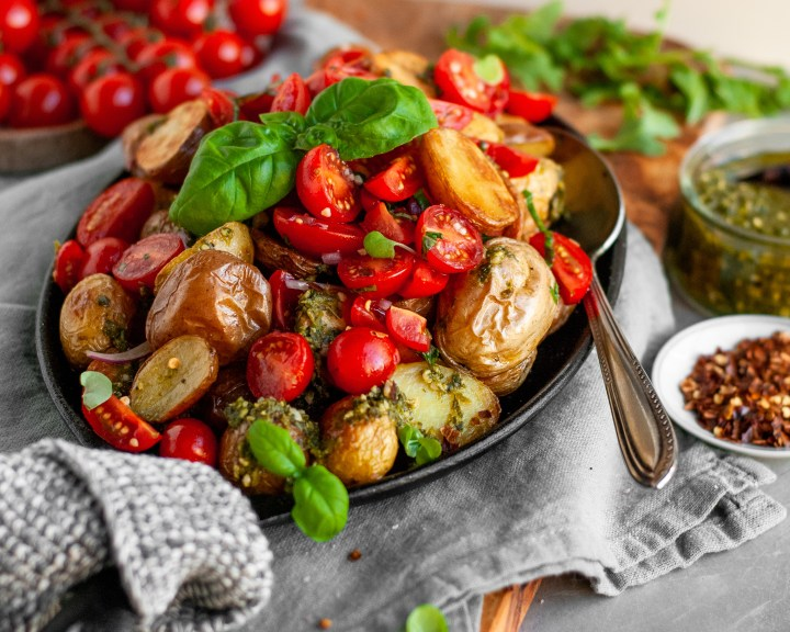 Roasted Baby Potatoes with Basil Pesto and Cherry Tomato Bruschetta being served with extra pesto and chili flakes
