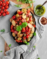 Roasted Baby Potatoes with Basil Pesto and Cherry Tomato Bruschetta being served with extra pesto and chilil flakes