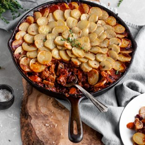 Vegan Savory Skillet Stew with Baby Potato Topping being served