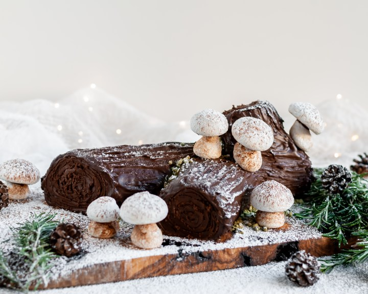 "Vegan Chocolate Yule Log with Meringue Mushrooms served on a plank covered in icing sugar ""snow"""