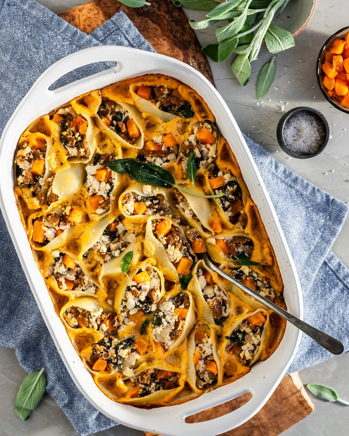 A close up of Vegan Roasted Butternut Squash, Sausage and Tofu Sage Ricotta Stuffed Shells in a baking dish