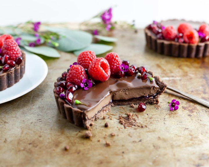 Chocolate Raspberry Dream Tart with a slice missing revealing the chocolate and raspberry layers