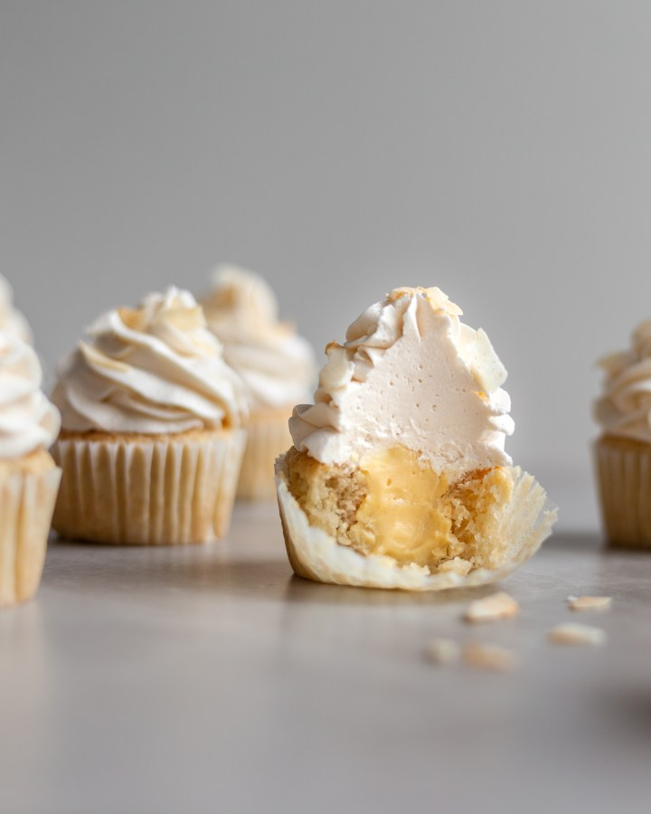 Vegan Coconut Cream Cupcakes cut in half revealing the custard center