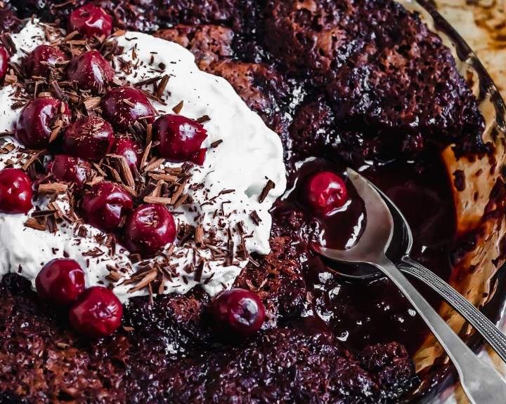 Saucy Cherry Chocolate Fudge Cake close-iup, being served with coconut whipped cream and morello cherries