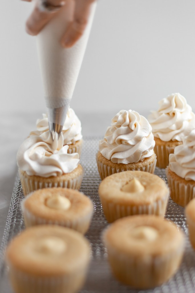 Vegan Coconut Cream Cupcakes being topped with coconut frosting
