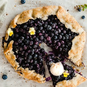 Vegan Blueberry Ginger Galette served with vegan ice cream and garnished with pansies