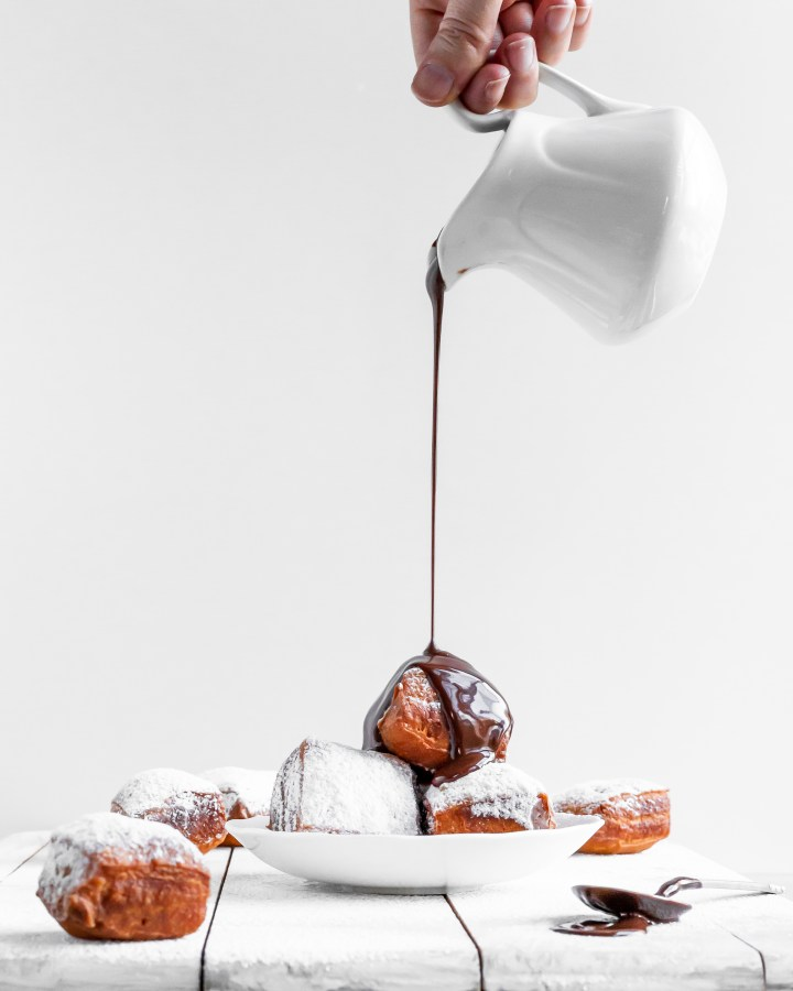 Vegan Beignets being covered in chocolate sauce