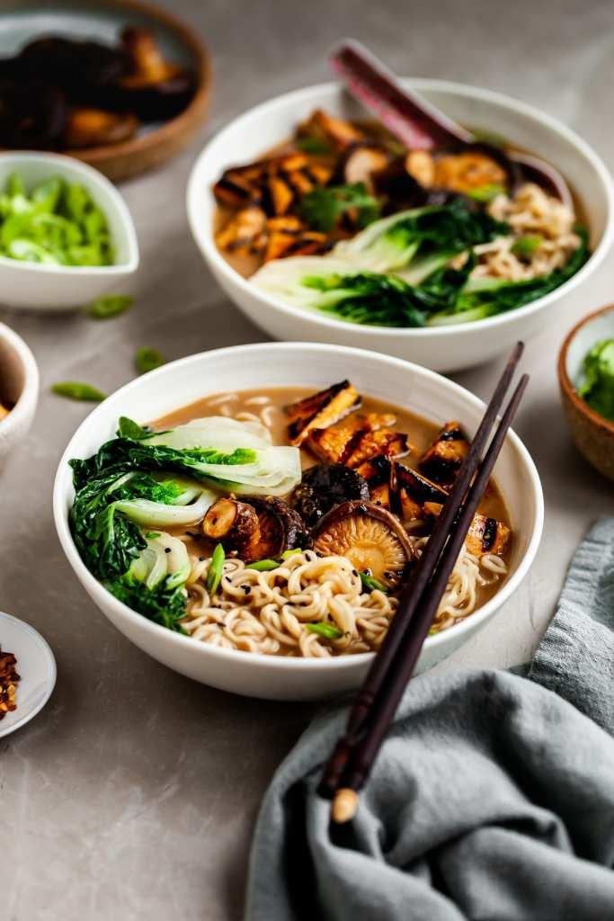 2 bowls of mushroom miso ramen and a few bowls of garnishes