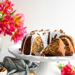 Vegan Hummingbord Cake with Vanilla Glaze sliced and sitting beside a vase of pink tulips