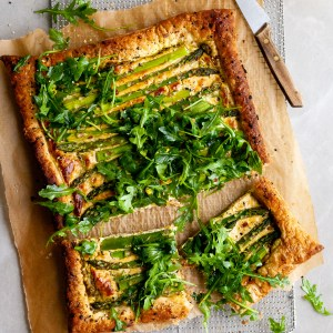 Vegan Asparagus and Pesto Cashew Cheese Tart with Lemon Arugula on colling rack and 2 pieces cut