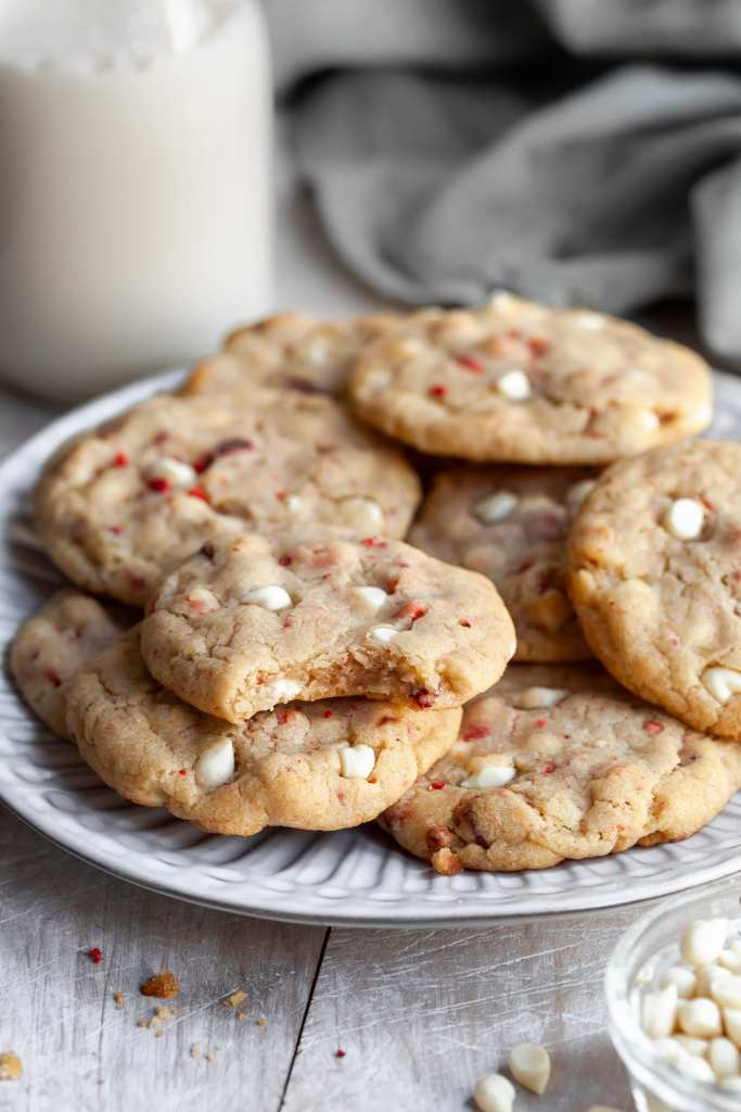 A plate of strawberries and cream cookies with a bite taken out of one revealing the chewy interior.