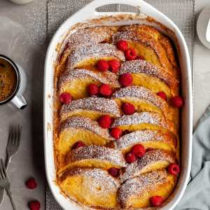 Vegan Lemon Raspberry French Toast Bake in a white casserole dish, garnished with fresh raspberries