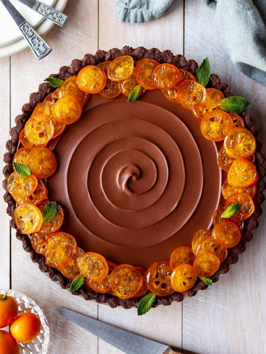 Flatlay of Vegan Chocolate Orange Tart with Candied Kumquats, ready to be sliced and served