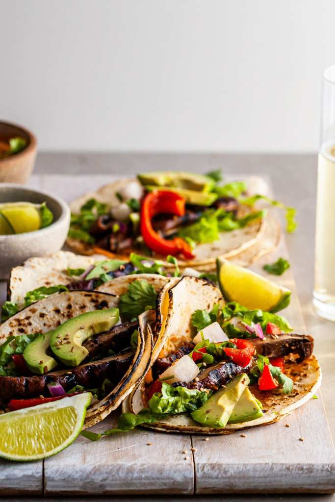 Close up of Korean Portobello Taco served with lime wedges