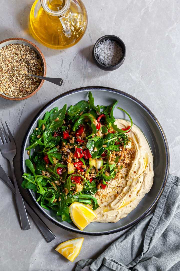 Looking down on a bowl of farro salad over hummus, served with lemon wedges and dukkah
