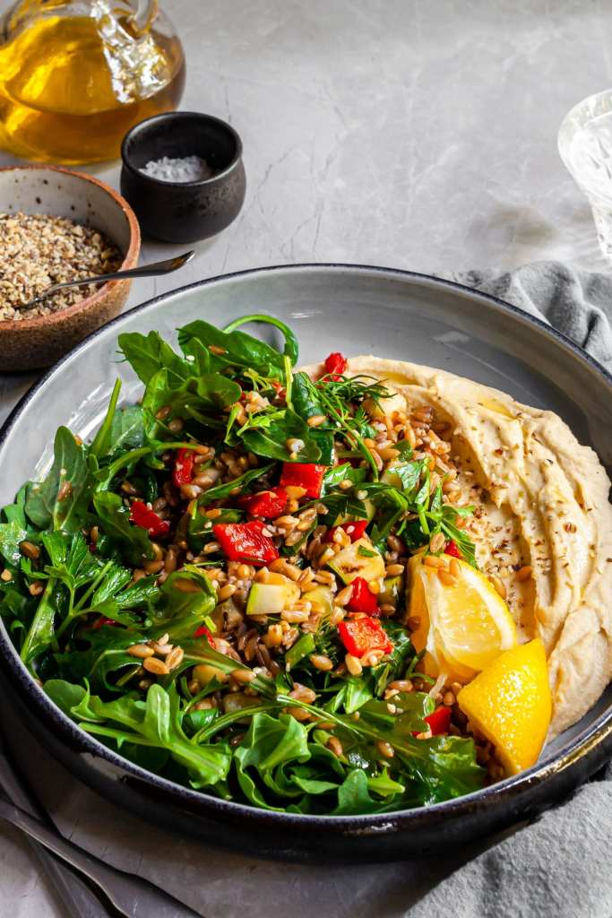 Herby Farro and Grilled Vegetables Salad served over Hummus with fresh lemon wedges and dukkah