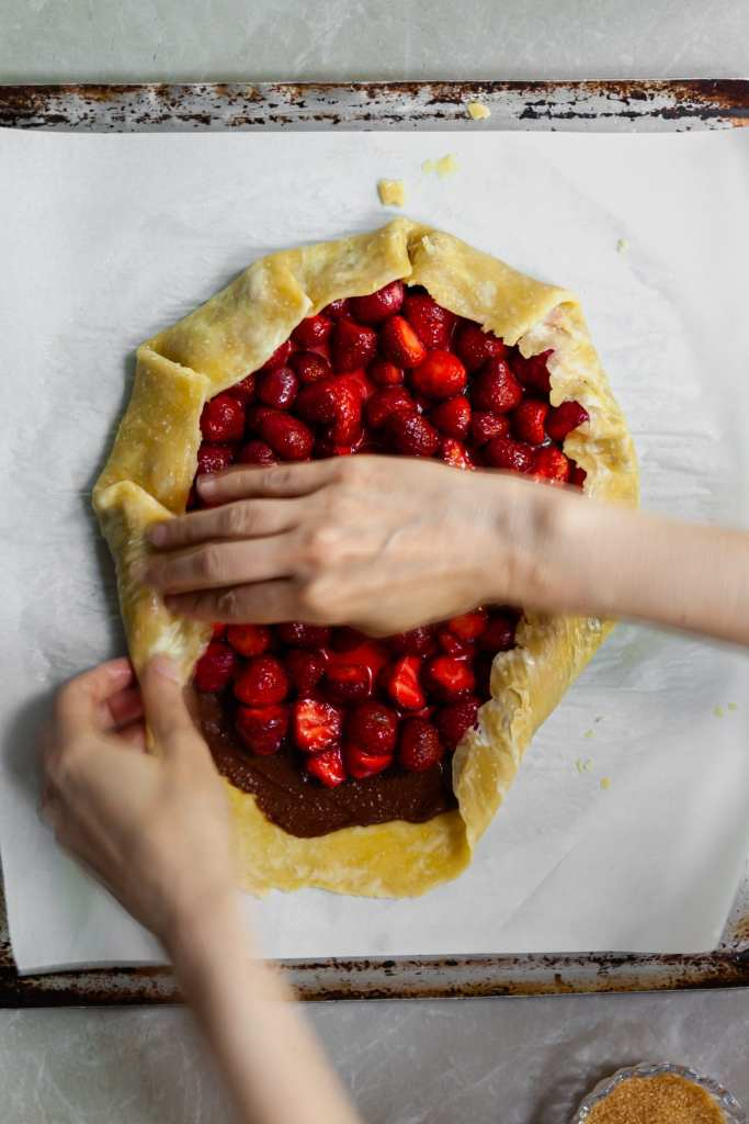 Folding the crust over part of the filling containing the hzaelnut chocolate spread and fresh strawberries