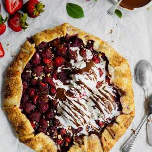 Fresh Strawberry Galette with Hazelnut Chocolate Spread warm from the oven, served with 3 scoops of vegan vanilla ice cream and chocolate sauce. Ready to be cut.