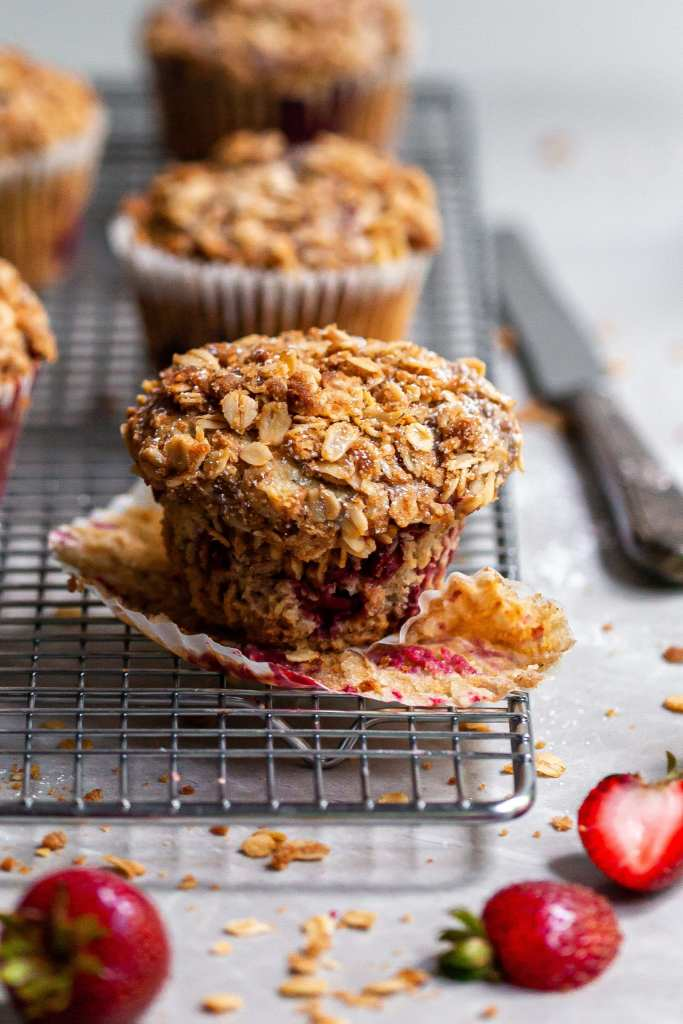 Close-up of a Vegan Roasted Strawberry & Oat Streusel Muffin sitting next to fresh sliced strawberries