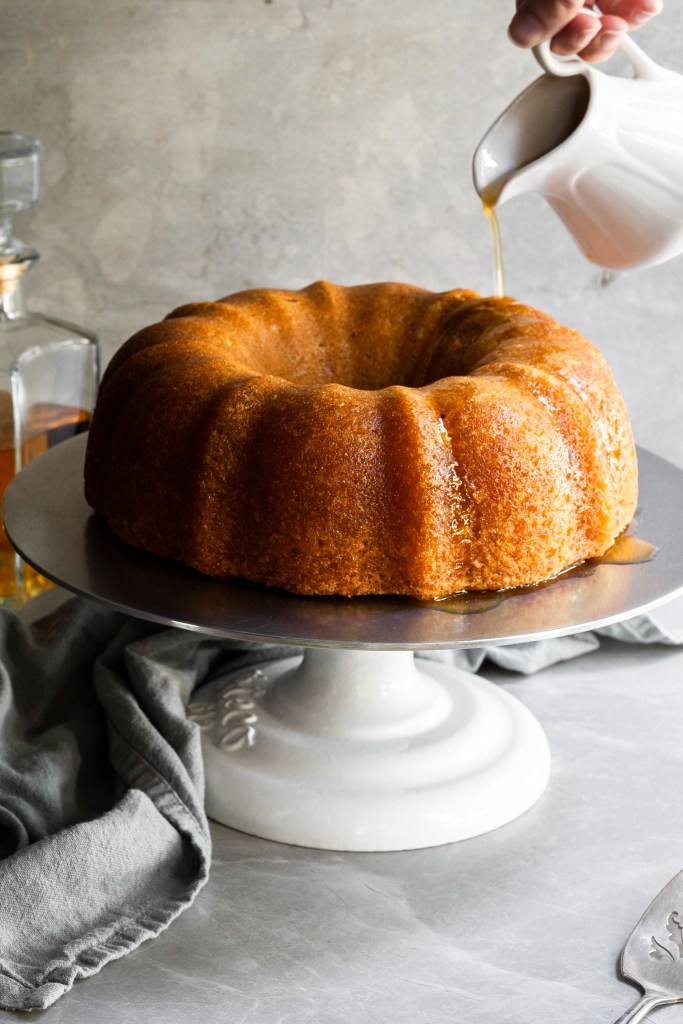 Vegan rum bundt cake on a cake stand and a stream of rum sauce being poured over the top