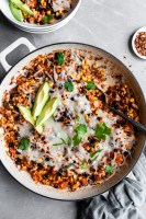 White enamel skillet filled with baked mexican inspired rice served with avocado slices