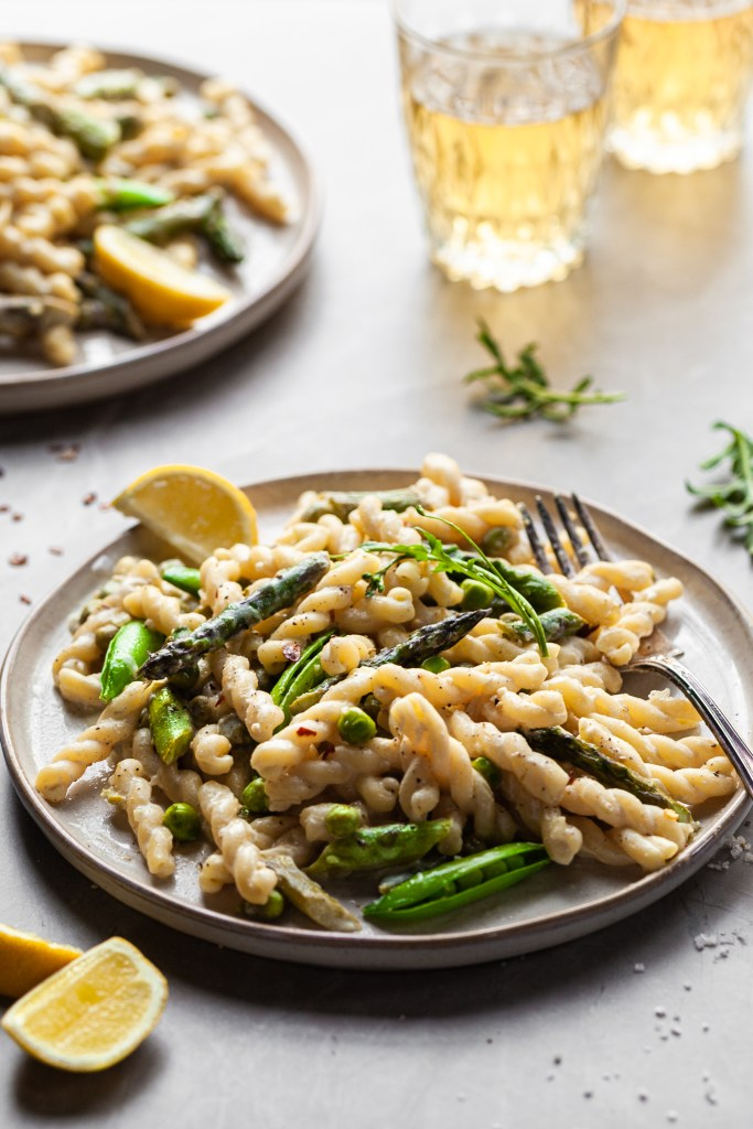 Side view of a plate of gemelli pasta in a light cream sauce with asparagus and spring peas with glasses of wine in the background